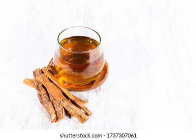 Tea and bark of cat's claw plant on wooden background, uncaria tomentosa