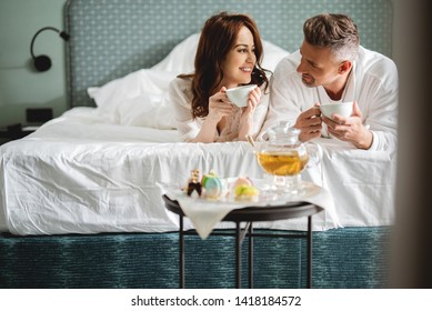 Tea in bed. Man and woman relaxing in their hotel room and smiling to each other while lying on the bed with cups of tea in their hands