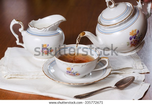Tea being poured into cup, tea set on wood