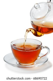 Tea being poured into glass tea cup isolated on a white background.