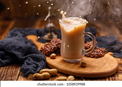 Tea with biscuits in a glass cup with a splash. Smoking, tea with milk and chocolate biscuits with nuts for breakfast are spilled from the cup.