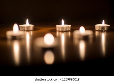 tea candles symbol of Christmas and the holidays, a group of candles in reflection flickering flame, positive and soothing energy