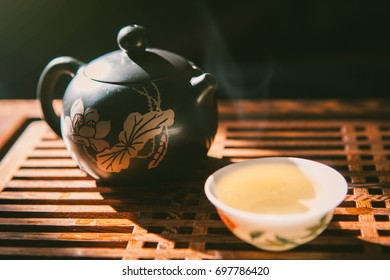 Tea ceremony with chinese puer greeen tea. Teapot and a cup of green puer on wooden table with small amount of vapour. Asian traditional culture.
