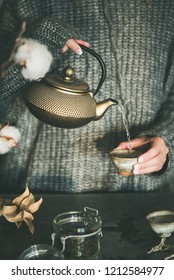 Tea ceremony. Woman in grey warm knitted winter sweater pouring green tea from golden iron pot into japanese ceramic cup in kitchen. Cold winter morning at home