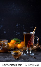 Tea with cinnamon and tangarine marmalade.  Clear glass dish. Dark food photo style. Christmas winter or autumn mood. Homemade citrus cinnamon and anise stars marmalade. Winter family tea