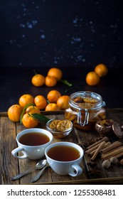 Tea with cinnamon and tangarine marmalade.  Clear glass and white dish. Dark food photo style. Christmas winter or autumn mood. Homemade citrus cinnamon and anise stars marmalade. Winter family tea