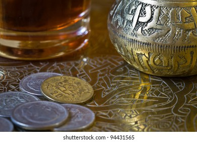 Tea and coins over an arabic tray