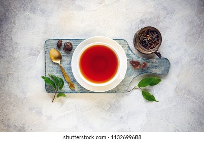 Tea composition with cup of tea, dried and fresh tea leaves and rock of sugar