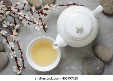Tea concept, cup with tea and white teapot decorated with blooming spring tree branch, top view