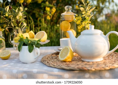 Tea concept, light cup with tea and white teapot decorated with lemons and oliva blooming yellow spring in the garden, top view. Teatime - Relax With Hot Tea In Zen Garden