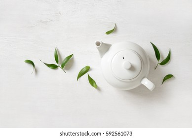 Tea concept, teapot with tea surrounded with green tea leaves, view from above
