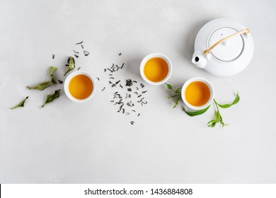 Tea concept with three white cups of tea and teapot surrounded with fresh green tea leaves and dry leaves,  top view composition on concrete background with copy space.
