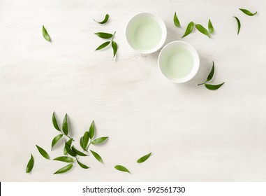 Tea concept, two white cups of tea surrounded with green tea leaves, view from above, space for a text