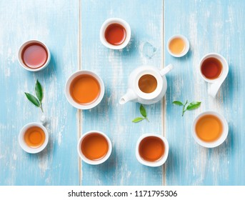 Tea concept,Teapot and cup of herbal tea with green tea leaves on blue table ,top view
