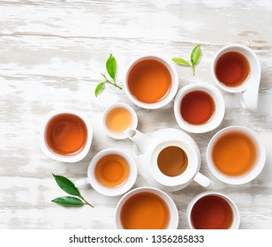Tea concept,Teapot and cup of herbal tea with green tea leaves on wood,top view