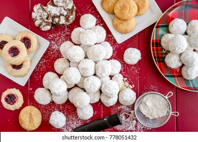 Tea cookies rolled in powdered sugar, arranged in shape of a Christmas tree surrounded by a variety of Christmas cookies