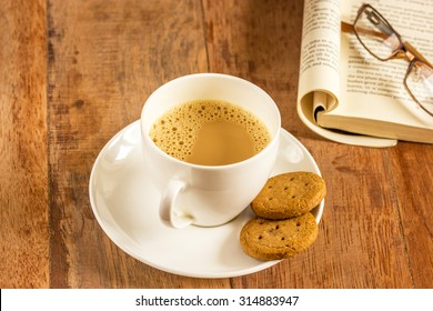 Tea with cookies in white cup plate with book and spectacles