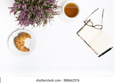 tea, croissant , glasses , notebook on a white desk was flat