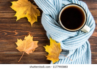 Tea cup and autumn leaves  on wooden background. Flu season in autumn, disease.