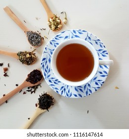 Tea cup with bamboo teaspoons and looseleaf tea on white surface