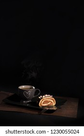 A tea cup and chocolate roll on a dish. Photo on black background. Copy space