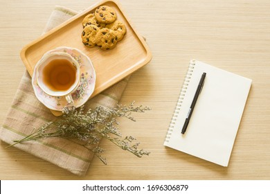 tea cup and cookies on wooden tray with flower and napkin on wooden table with blank notebook and pen