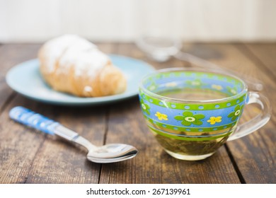 tea in a cup and croissant on a plate on a table, selective focus