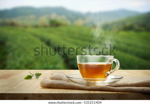 Tea cup with green tea leaf on the wooden table and the tea plantations background