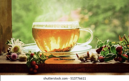 Tea cup with tea leaves on window.  Summer tea time.