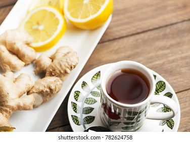 Tea cup with lemon and ginger on white plate. Infusion.