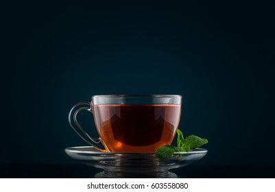 Tea Cup with mint leaves on a dark background.