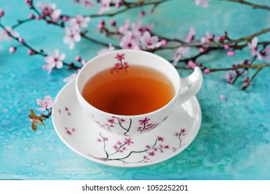 Tea cup on the blue background with the spring blossom branch, spring flowers