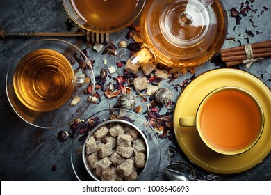 Tea in a cup on a metallic background in a composition with a cookware
