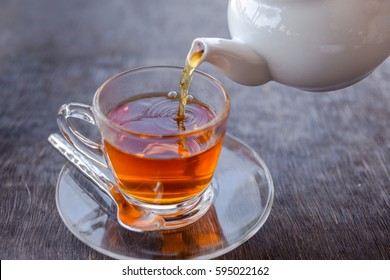 Tea cup on saucer, with tea being poured