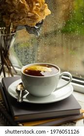 Tea cup on windowsil with rainy glass window. - Shutterstock ID 1976051126