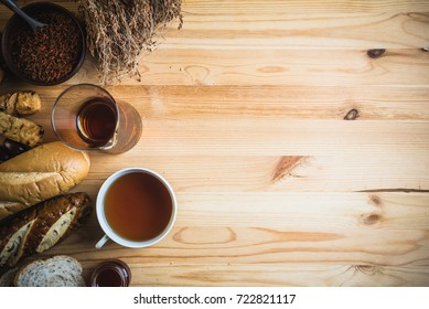 Tea cup with pitchers tea and bread around on wooden top table. Working space