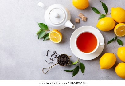 Tea cup and pot with lemon. Grey background. Copy space. Top view.