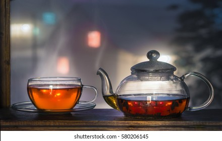 Tea cup with tea pot on window. Winter tea time.