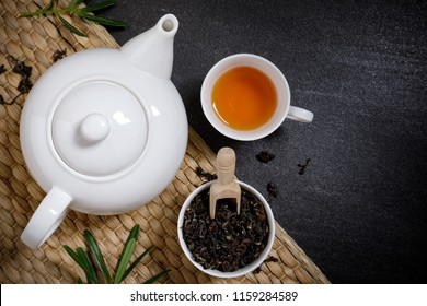 Tea cup with steaming jars and dry tea on the napery on the black stone desk background with copy space for your text.