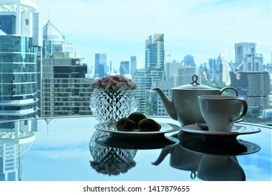Tea cup, teapot, Green Tea Daifuku ,crystal vase with pink carnations on the glass table and the view of the high-rise building outside.