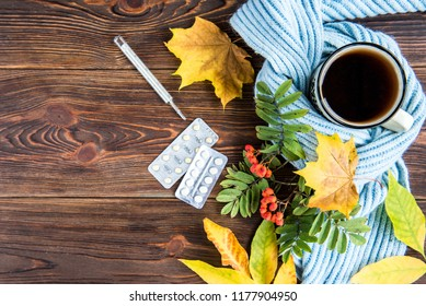 Tea cup with thermometer, blue scarf, pills and autumn leaves  on wooden background. Flu season in autumn, disease.