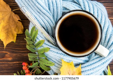 Tea cup with thermometer, blue scarf and autumn leaves  on wooden background. Flu season in autumn, disease.