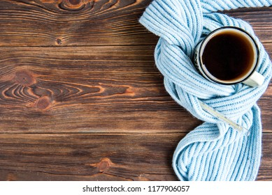 Tea cup with thermometer, blue scarf on wooden background. Flu season in autumn, disease.