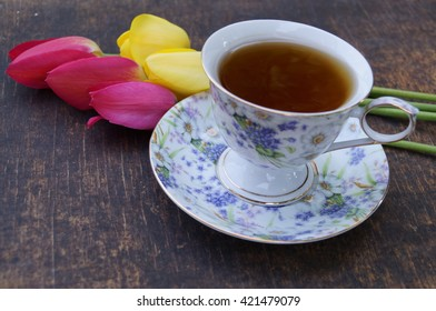 Tea cup, tulip flower, on wooden background