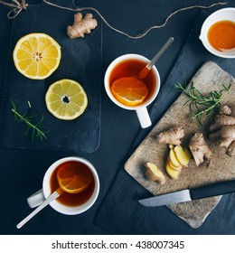 Tea cups with black tea, lemon, ginger