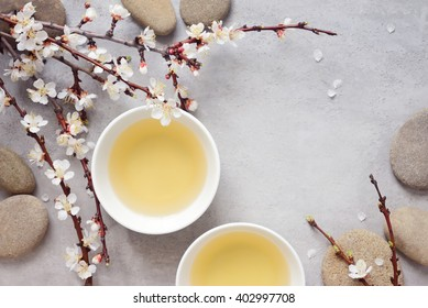 Tea cups with tea decorated with spring blooming branch, stylized photo, top view