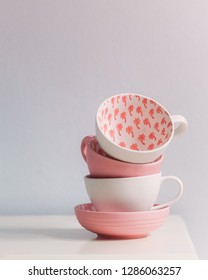 Tea cups stacked - pink/coral and white teacups and saucer on an off-white table, one teacup showing palm tree pattern in vivid coral. Neutral background. Space for text.