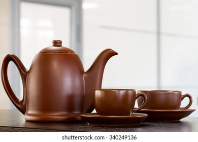 Tea cups with teapot on old wooden table