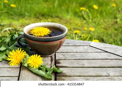 tea from dandelion  in a rustic earthenware cup on a wooden table against a blurred meadow with copy space, selected focus, narrow depth of field
