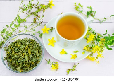 Tea (decoction) of medicinal herb St. John's wort (Hypericum) in a white mug, twigs and dried herb St. John's wort on a wooden background.